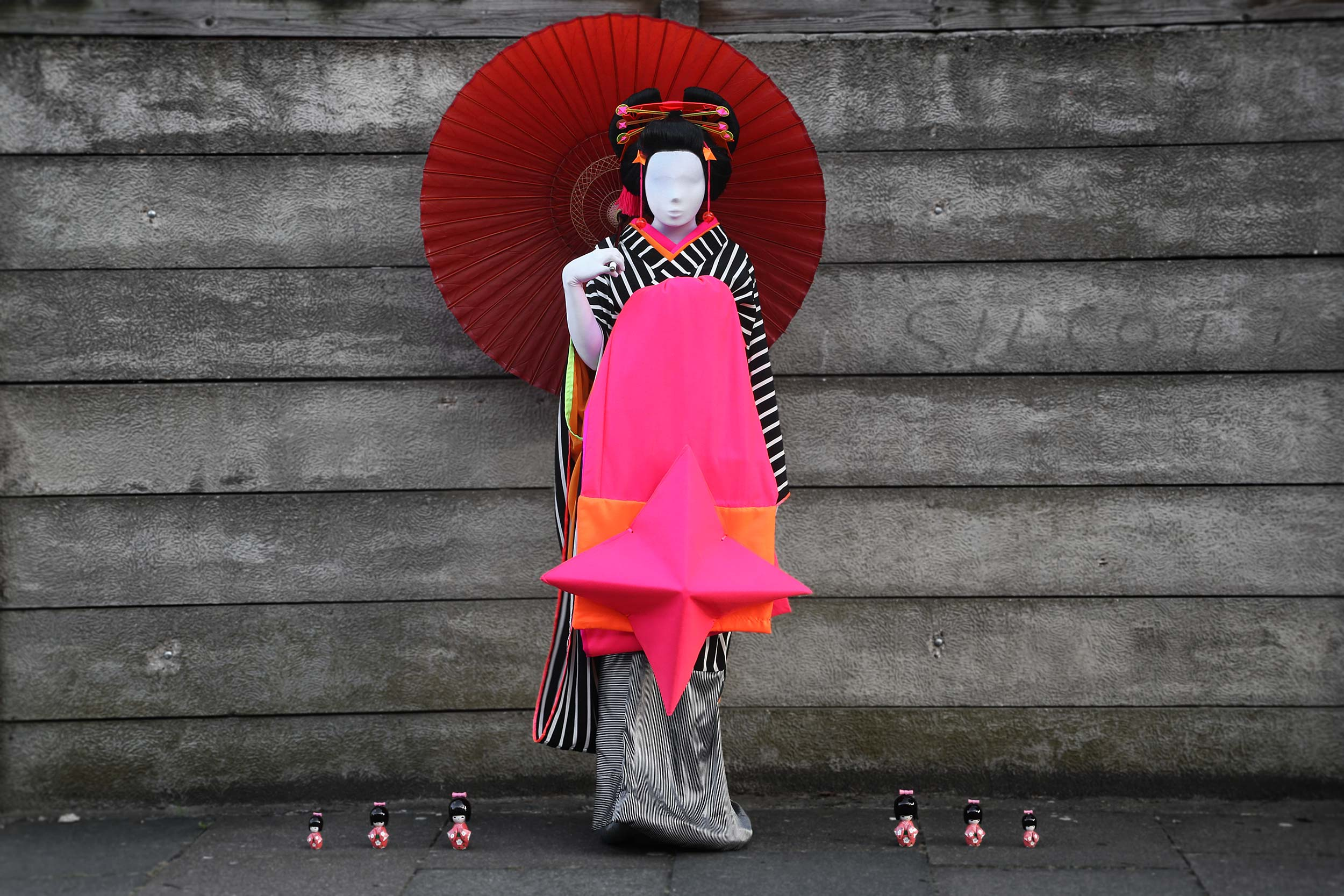 A woman dressed as a cyberpunk version of a japanese oiran holds a large red paper umbrella, stands with traditional kokeshi dolls by her side.