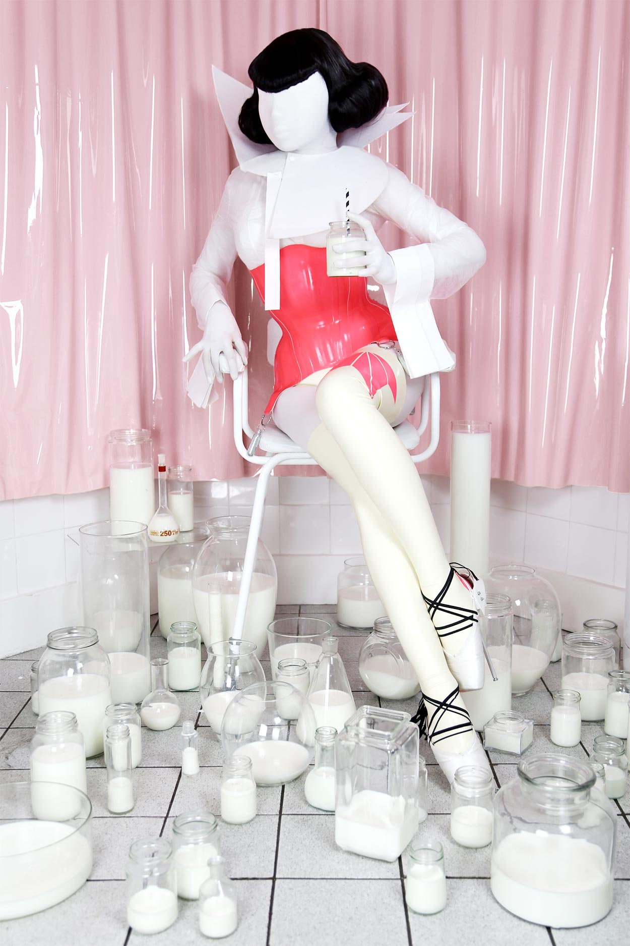 A doll-like woman is dressed in latex clothes and corset made by Milkshaken.net, is seated, surrounded by jars full of milk.