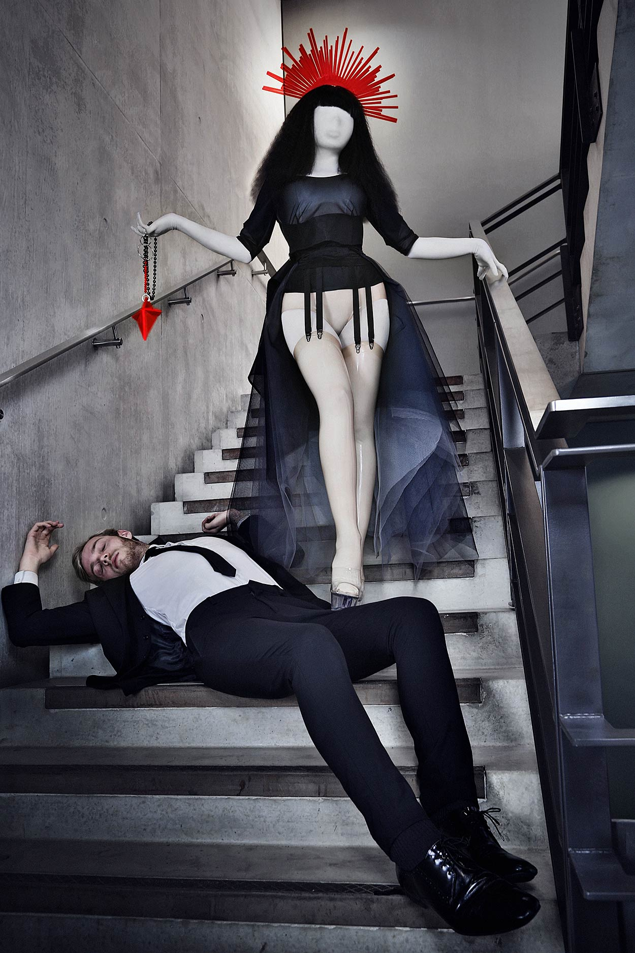 Reverse pieta: A voluptuous, saintly woman with a neon pink halo is wearing latex stockings and descending a flight of stairs, stepping on an unconscious man.