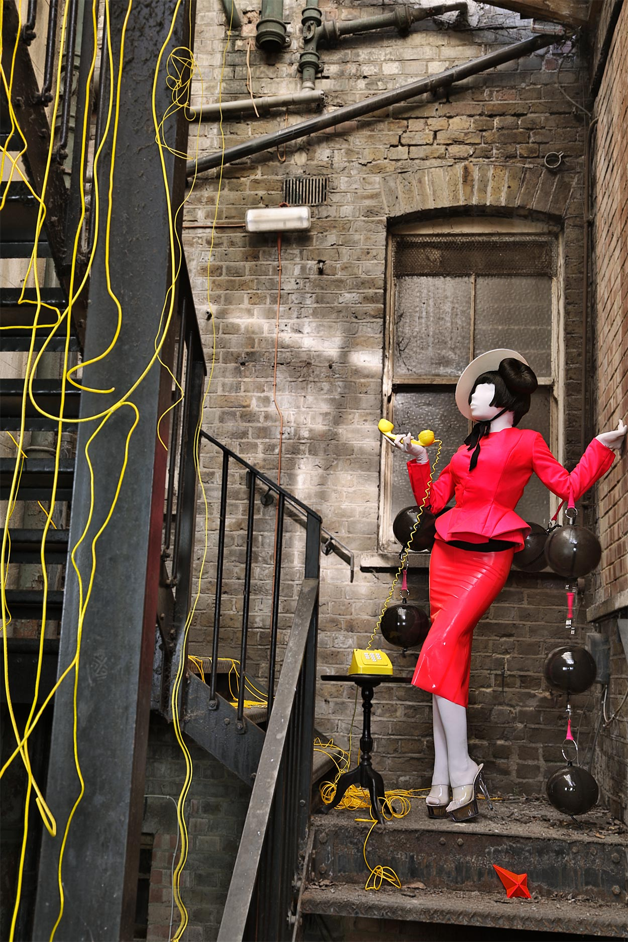 A woman dressed in a hot pink jacket and latex pencil skirt made  by Milkshaken.net, stands on a fire escape staircase speaking on an old yellow dial telephone.
