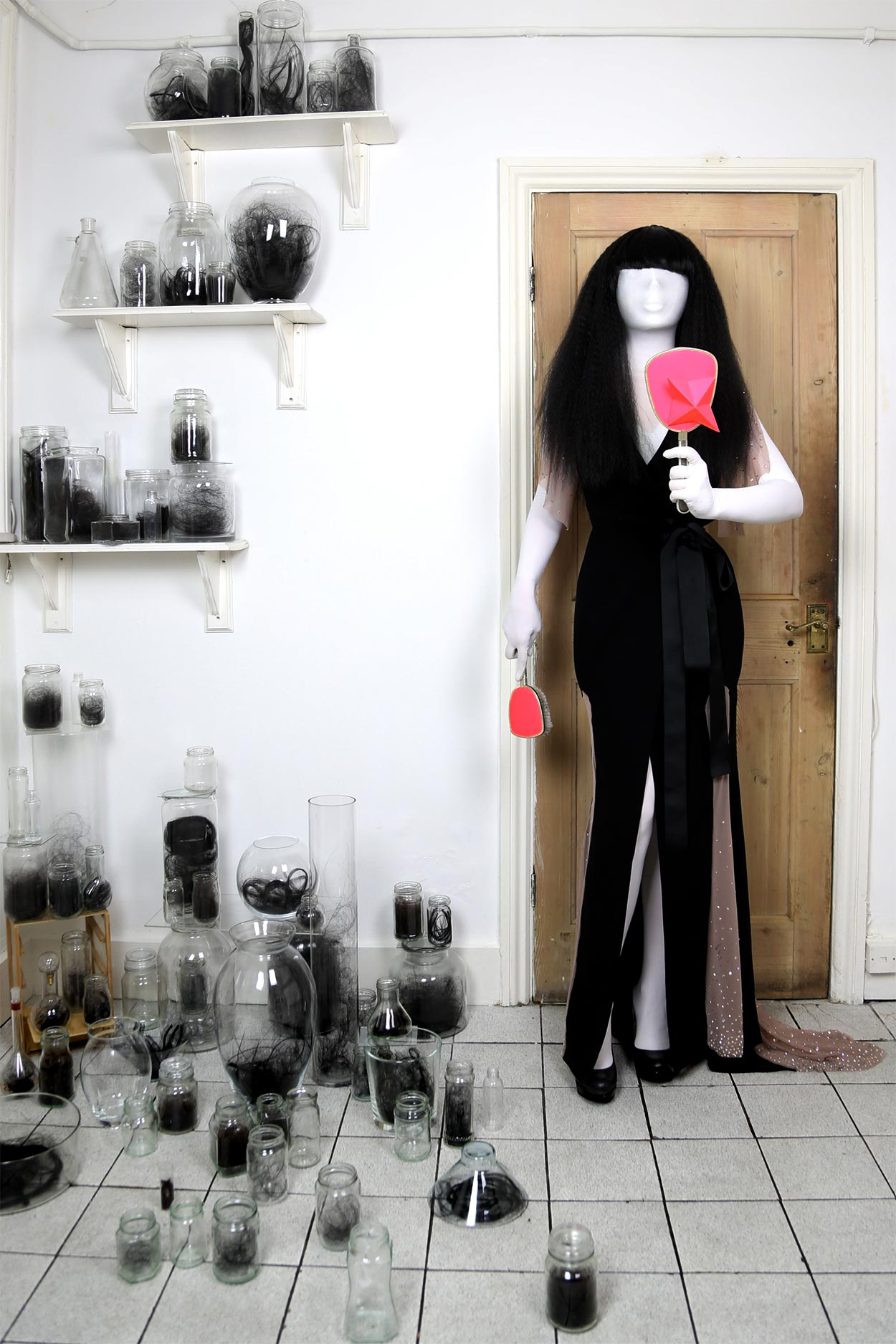 A woman wearing an Old Hollywood style gown made by Milkshaken.net, is holding a hand mirror and hairbrush, surrounded by jars of her own hair.