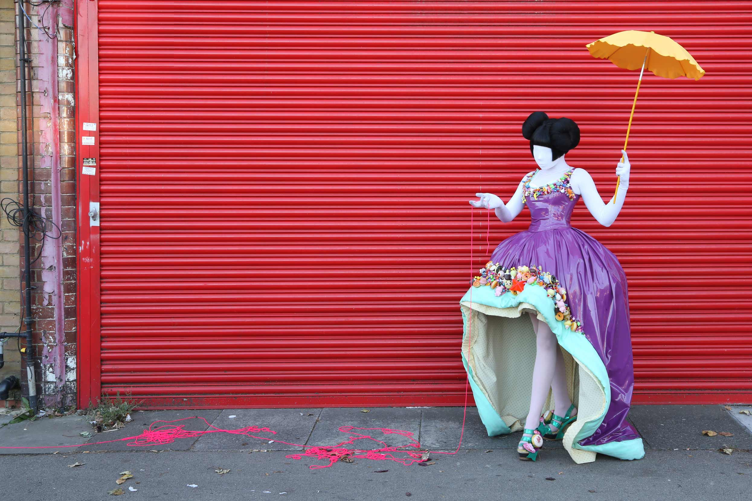A doll-like woman dressed in an extravagant purple vinyl dress made by Milkshaken.net holds a yellow parasol and follows a neon pink thread trail found on the street.