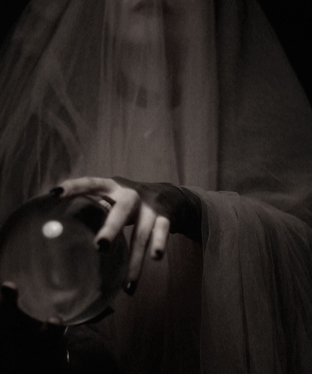 A doll-like woman with a white, featureless face like a mask, looks in the mirror and puts on white make-up.
