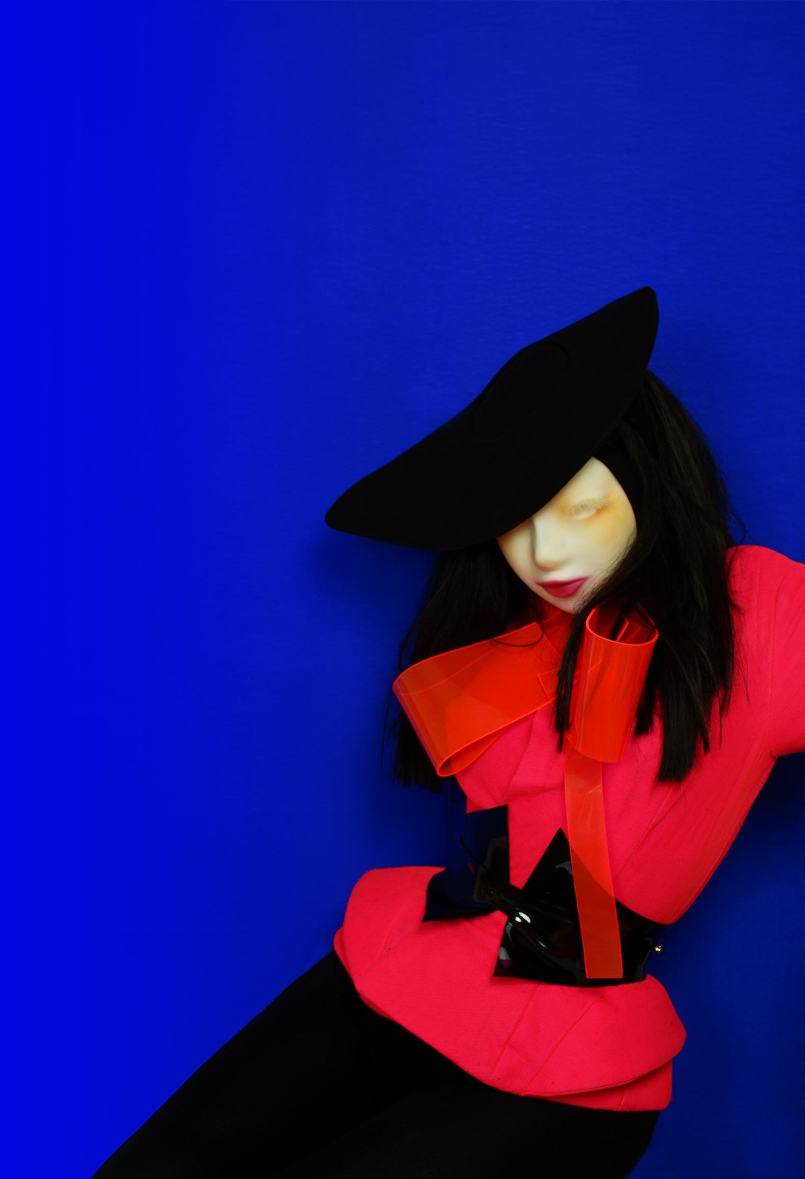 A doll-like woman wears a black cartwheel felt hat, a hot pink peplum jacket and a black vinyl underbust corset belt, made by Milkshaken.net