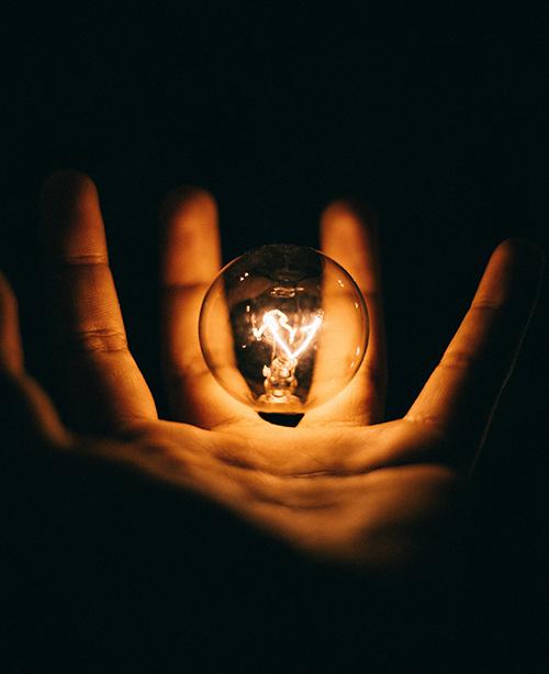 Lightbulb Lighting Up In Palm Of Hand