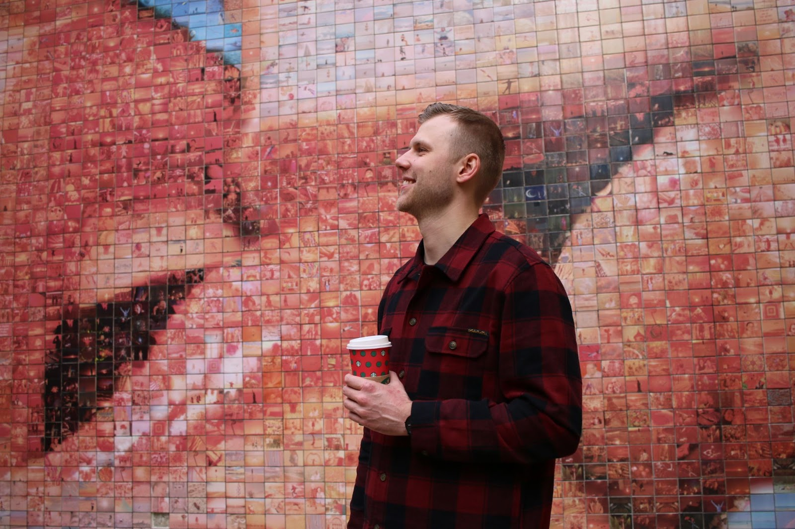 Julian Gumny holding a coffee cup in front of modern art wall