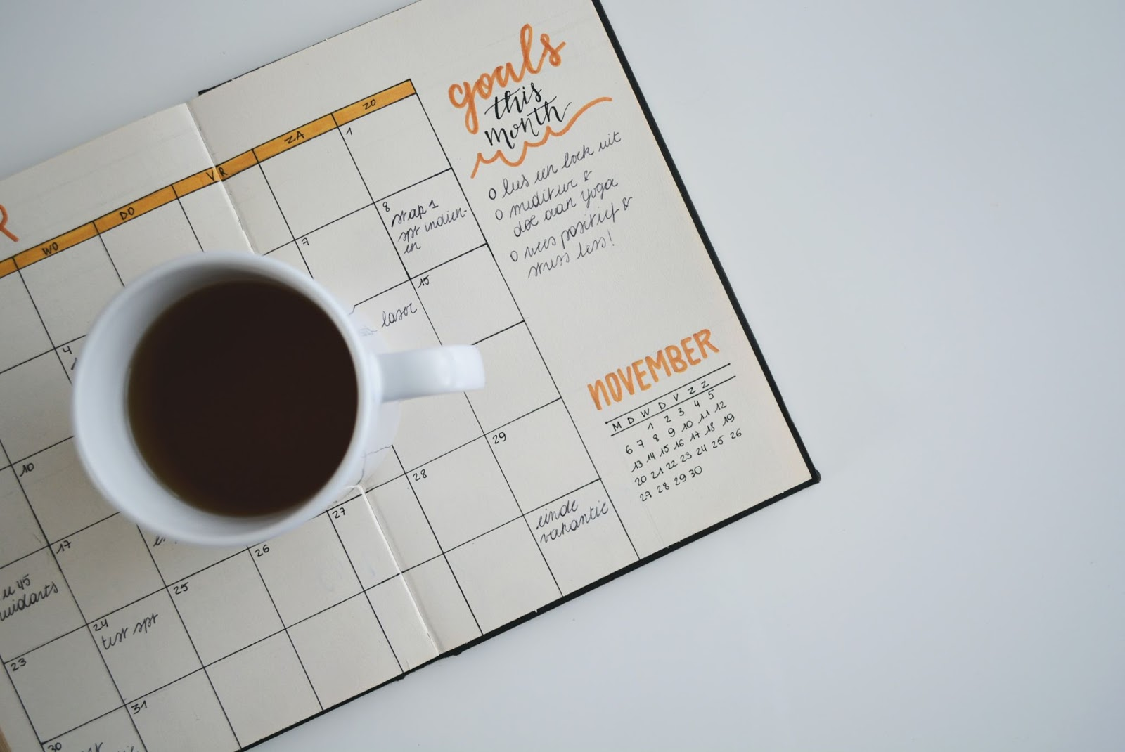 Cup of coffee on top of a monthly goals calendar