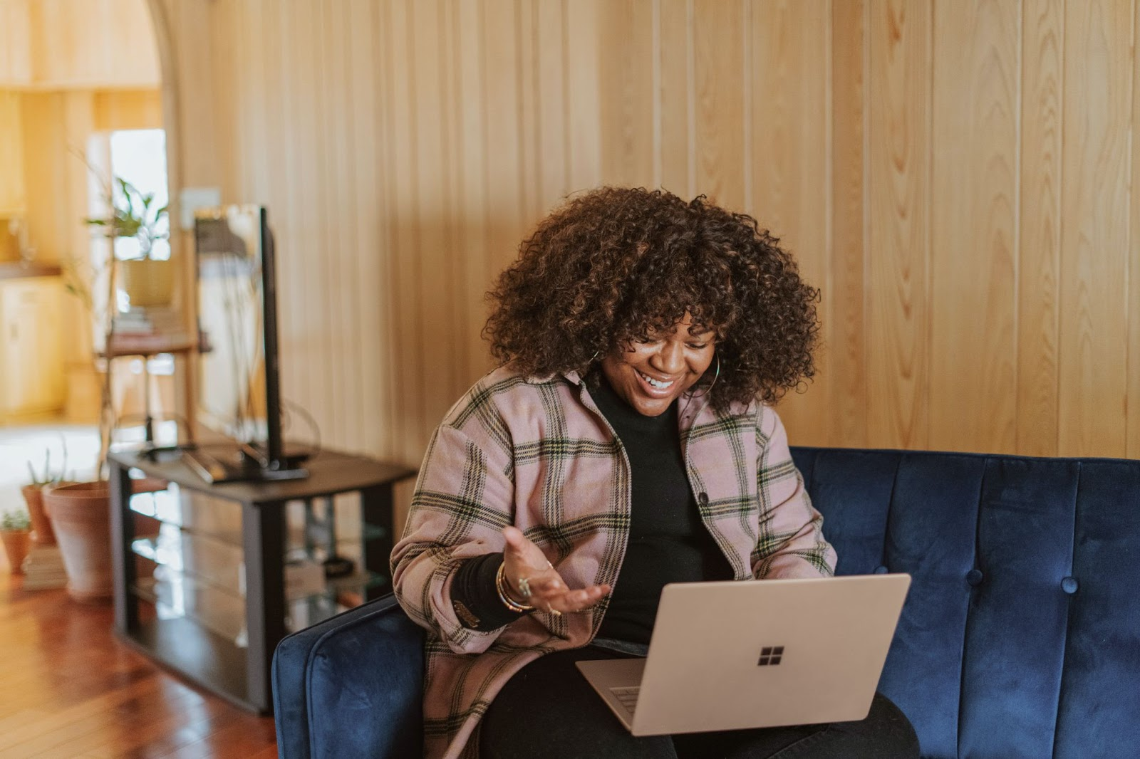 Woman sitting on couch while holding a laptop
