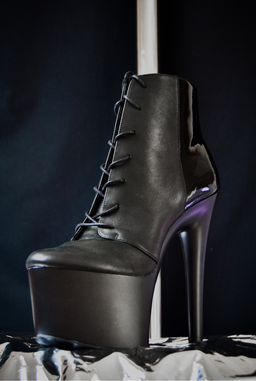 Dup Patent and Matte Black Ankle Boot in front of pole