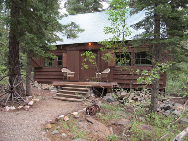 The recreation building at Gold Lake Lodge with gravel path leading to the front door.
