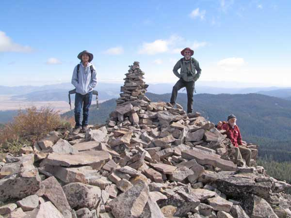 The rocky top of Haskell Peak with hikers and a tall cairn of rocks.