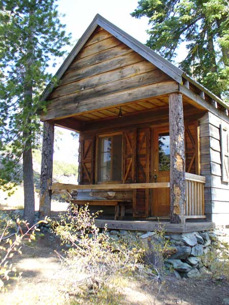 Davis Cabin outside with covered porch and bench, a three person cabin