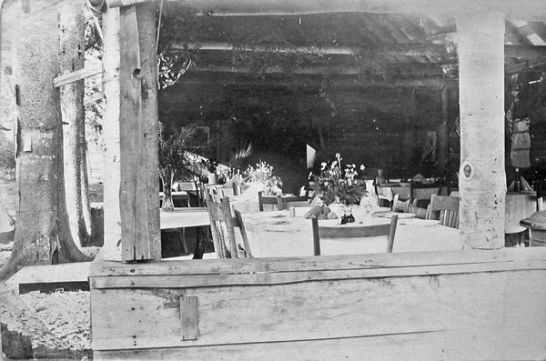 Dining Room in a tent cabin in the 1920's set up with tablecloths and wildflowers.