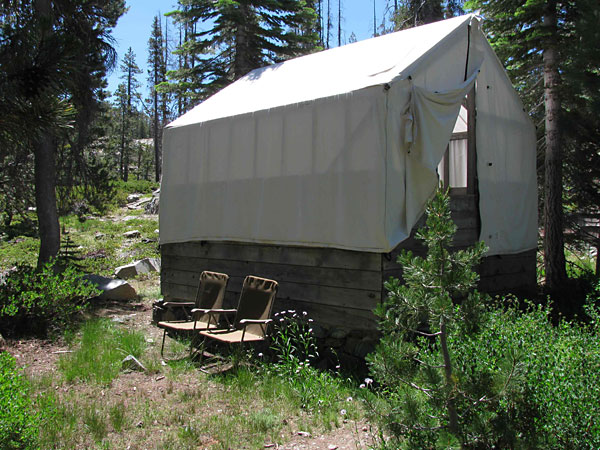 Tent cabin with wood siding and canvas tent, chairs sitting on the ground
