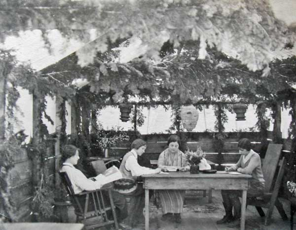 The first Recreation Hall in the early 1920's was in a tent cabin. Guests enjoying the peace and quiet, reading and writing.