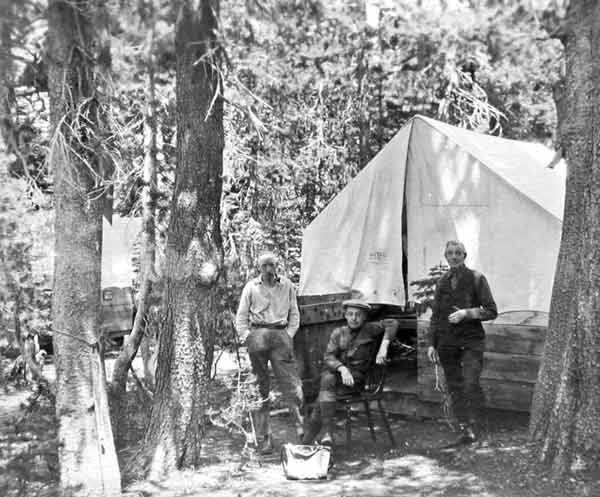 Tent Cabin in the 1920's with three men relaxing outside
