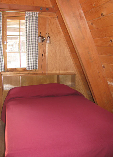 The double bed downstairs tucked in the corner of the main room  with a window above it.