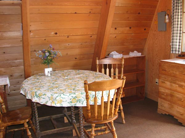 Inside A-Frame looking at dining space with round table and wood chairs