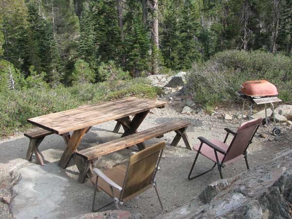 A-Frame outside dining area behind the cabin with picnic table, folding chairs and barbeque.