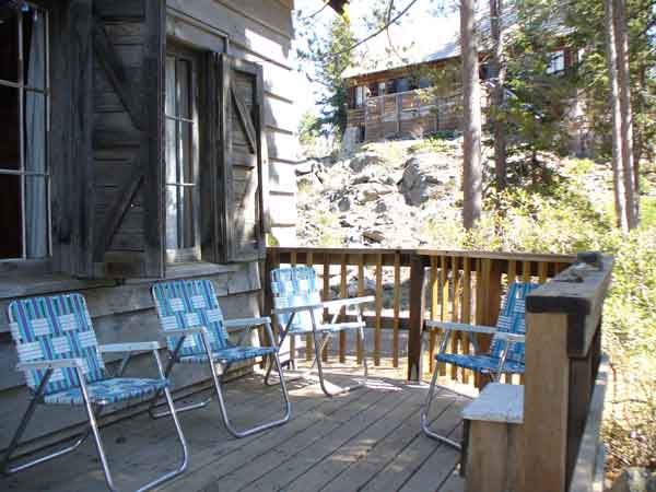 Front porch of Andrews Cabin with folding chairs with a view of the Dining Hall on a hill above.