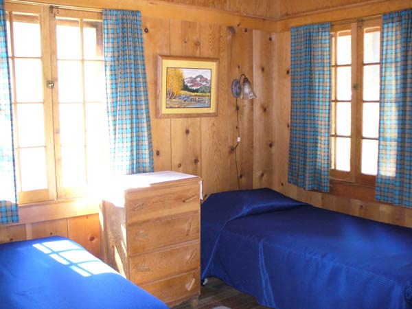Bindee Cabin's double and single beds with wood frame windows and dresser.