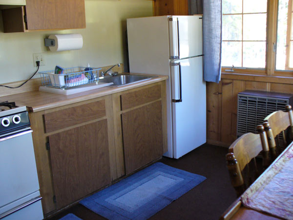 Childs Cabin dining area and kitchen. There is an apartment size refrigerator and a four burner stove with an oven.