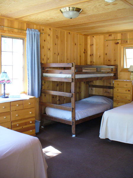 Childs Cabin bedroom with a double bed on the left, twin bed to the right, and a bunk bed between them.  Two dressers in the wood paneled room