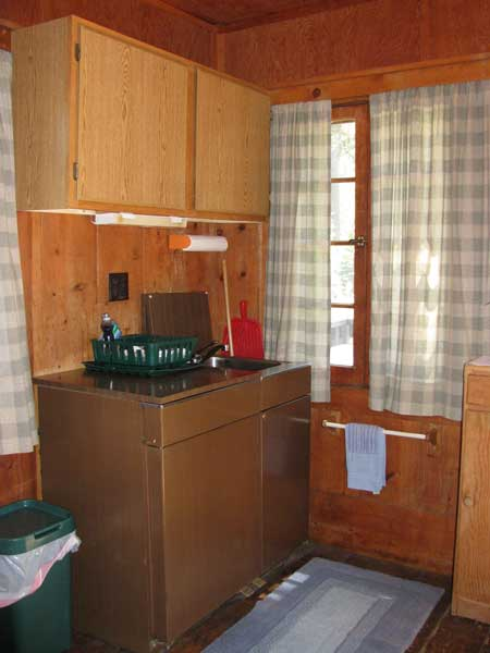The kitchen unit in Cromwell is a compact unit with a small refrigerator, two burners and a sink. Dishes and pots and pans are in the closed cabinets.
