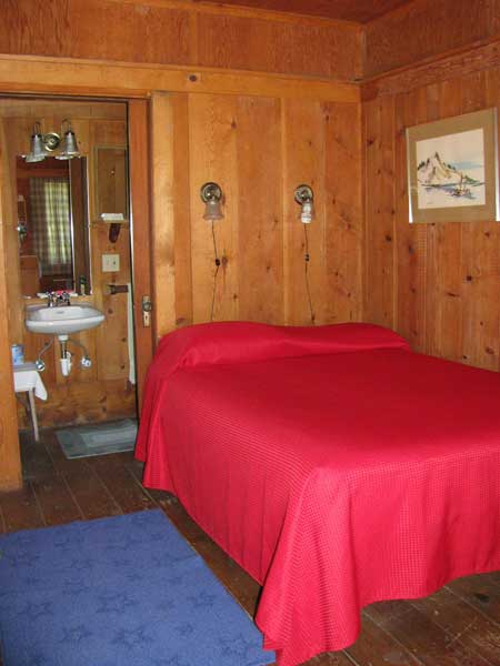 The double bed in the wood paneled cabin with the bathroom just a few steps away.
