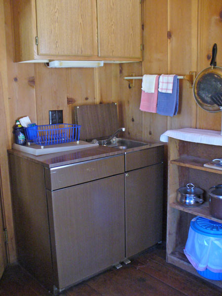 The compact kitchen in Davis Cabin has all the pots and pans within reach. The kitchen unit has a small refrigerator, two burners and sink.