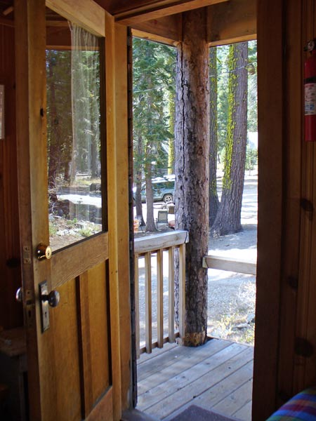 Davis Cabin door opens out to a covered porch with a view of the grounds.