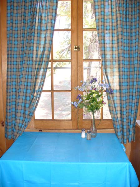 Dining table with flowers in a glass vase inside Bindee Cabin with view through the window above the table.