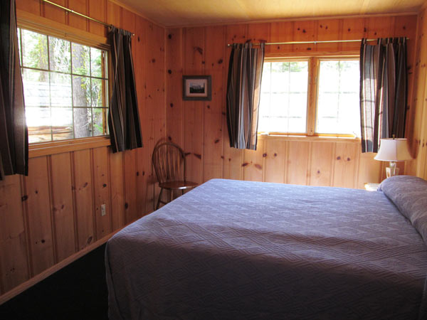 Drew Cabin has a separate bedroom with a king bed and large windows and wood paneled walls.