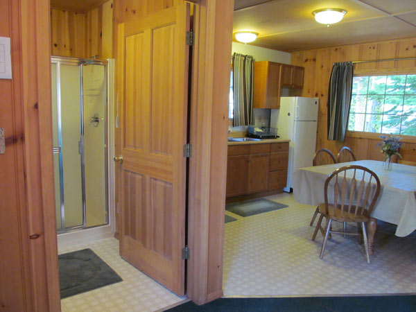 The bathroom is just off the front bedroom and kitchen. It has a large shower with glass doors.