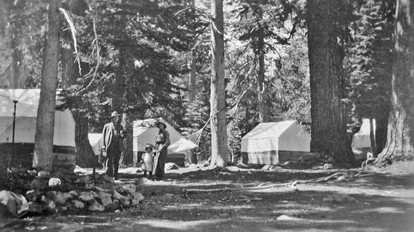 A view of the center of Camp Elwell with several tent cabins, Mrs Drew and Miriam Drew in foreground