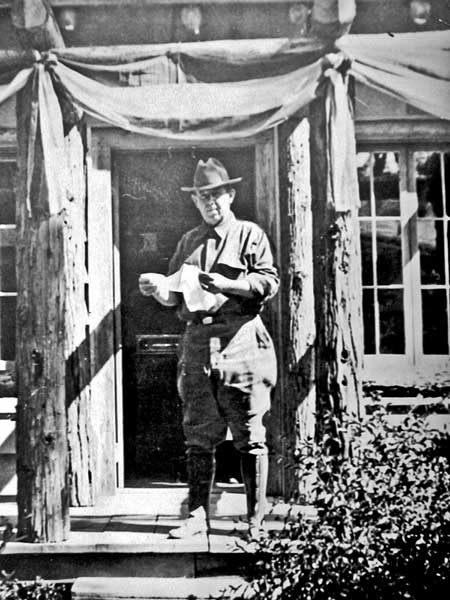 Bill Drew reading from a paper at the door of the office in the 1920's, the office is now Andrews Cabin