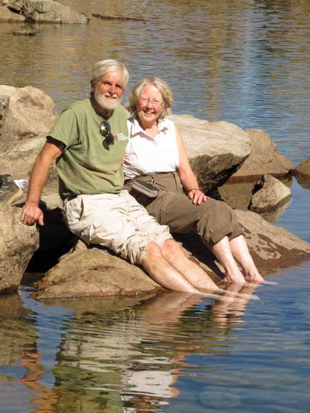 John and Sugie Barker sitting beside Young America Lake with feet in the water