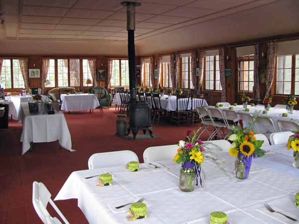 The Dining Hall set up for a wedding dinner with white tablecloths and festive yellow and purple flowers.