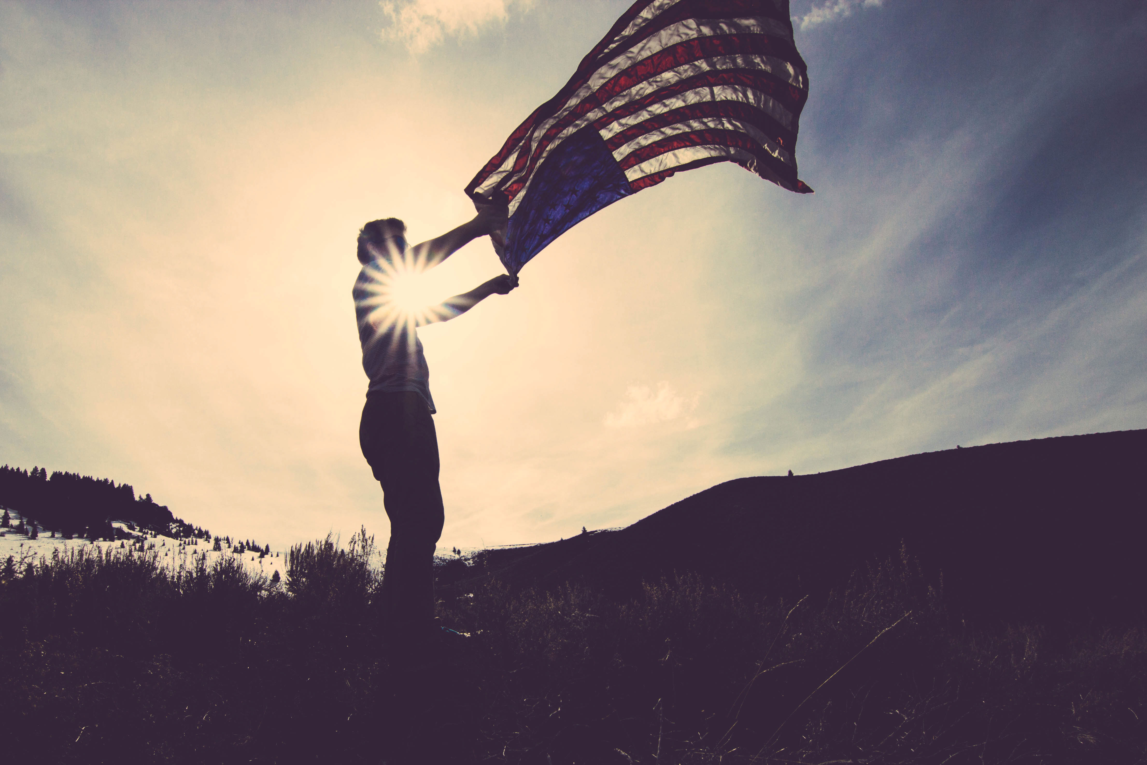 A person waving an American flag in the air