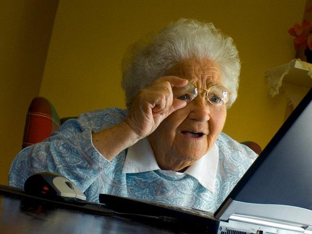 An elderly woman looking at her laptop confused