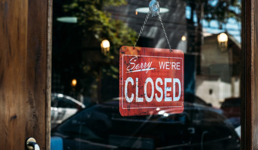 "A ""sorry we're closed"" sign hanging on a glass door"