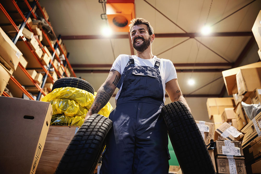 store worker carrying tires