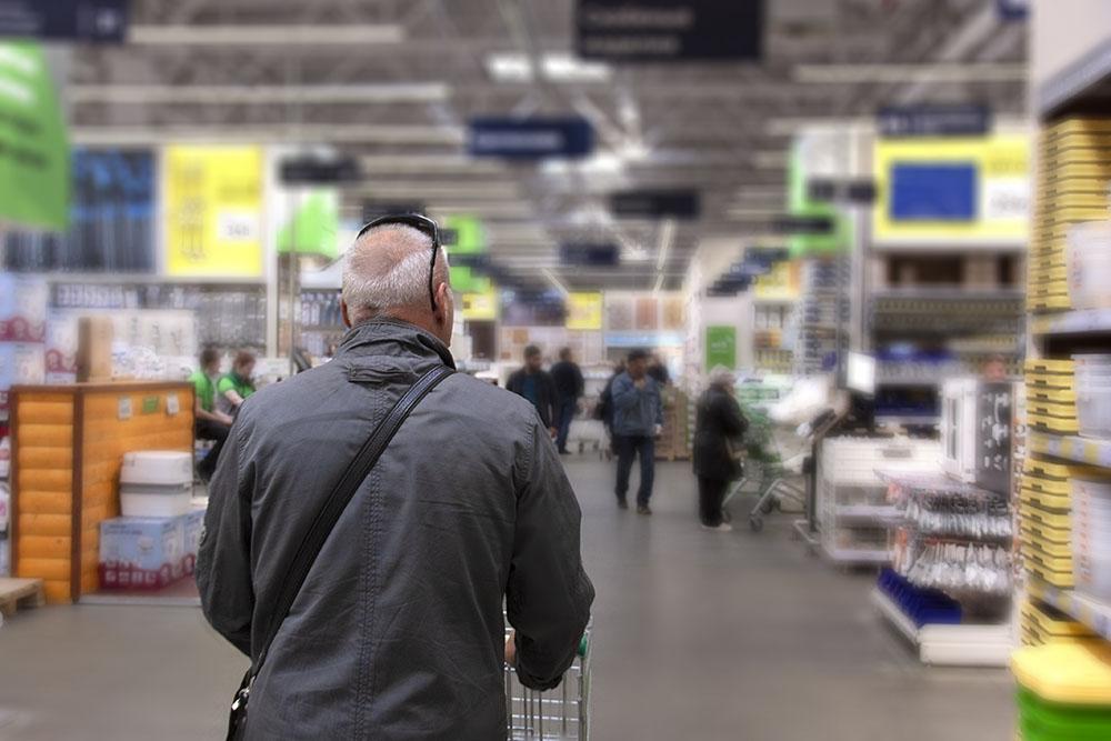 Man pushing cart through store