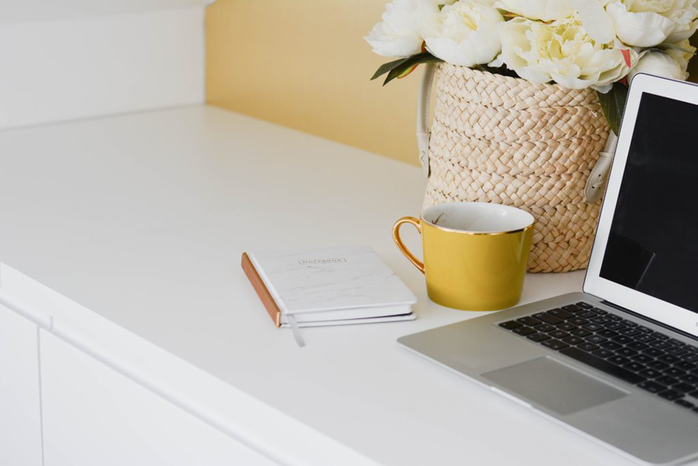 A cute desk with a laptop and yellow mug