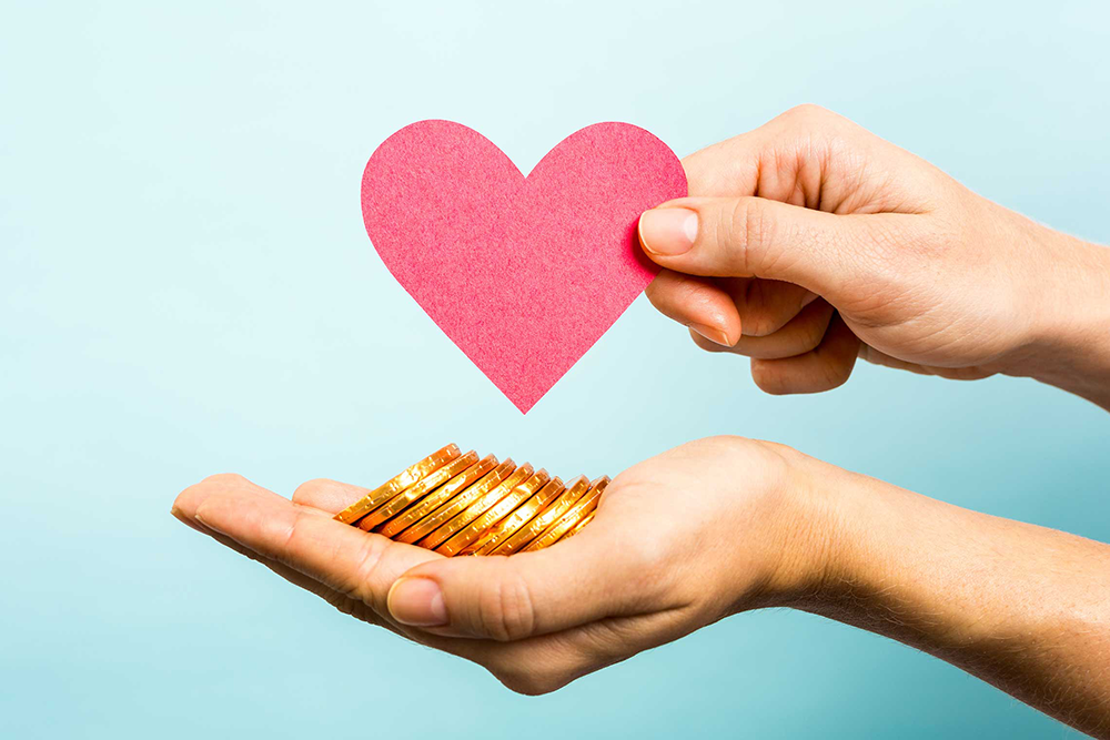 One hand holding gold coins, and another hand holding a paper heart