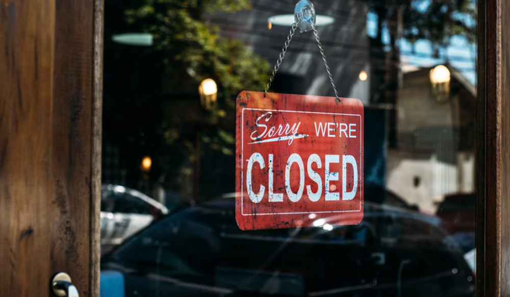"""A """"sorry we're closed"""" sign hanging on a glass door"""
