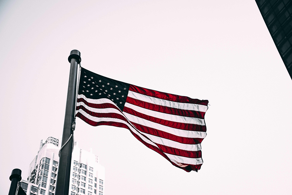 The American flag waving on a pole in the city