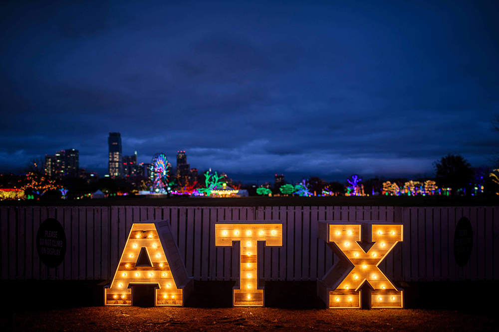 A lit up sign of the letters ATX at night time
