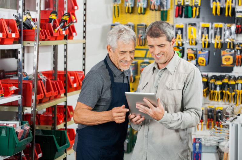 two men looking at ipad inside hardware store