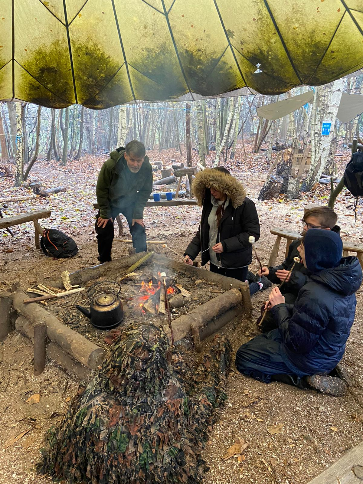 Thrive students around fire pit in woods. The Mix Stowmarket